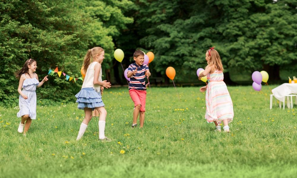 Niñas y niño jugando con globos en parque o jardín